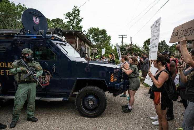 A group of protesters peacefully block an armoured police van