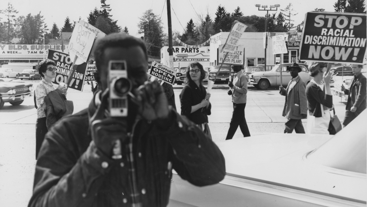 A black and white photo of an activist filming a civil rights protest