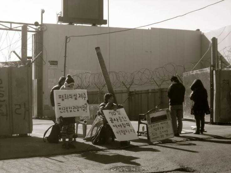A handful of activists sit in front of the gates of the naval base being built on Jeju Island