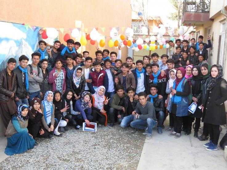 Roughly fifty young people gather for a photo in a street. Some are wearing blue scarves