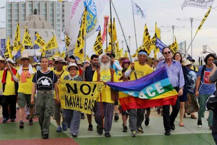 "A large number of people march towards the camera. They are wearing yellow and carrying yellow flags reading ""No Naval base"""