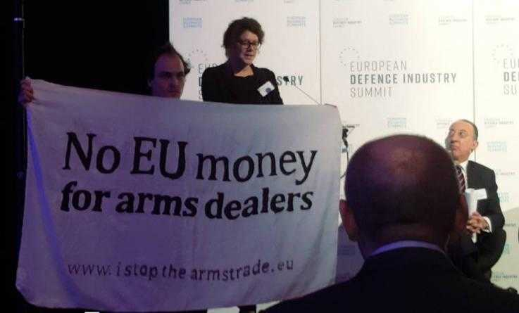 "An activist stands on a stage at the microphone. Another holds a banner reading ""No EU monday for arms dealers."" A man in a suit on the stage looks on."