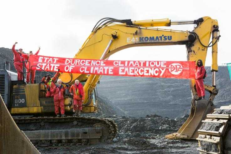 Protesters hang banners from a digger inside a coal mine, as part of a direct action against climate change