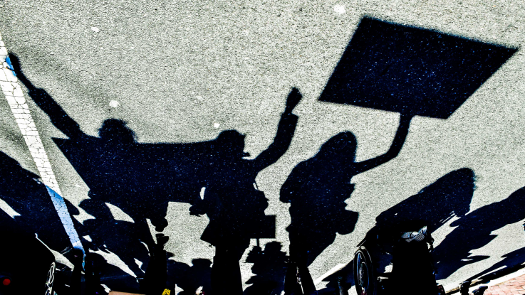 Silhouettes of activists marching down a street