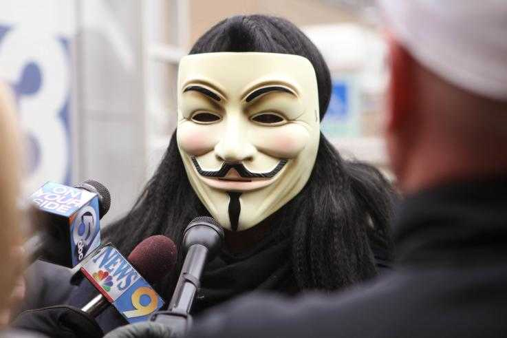 An activist wearing a guy fawkes mask speaks to the media