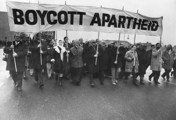 "People march under a ""Boycott Apartheid"" banner"