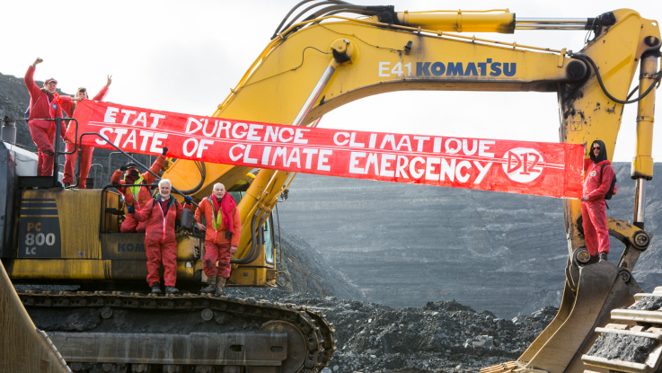 "Climate activists occupy a digger in a coal mine, and hang a large red banner reading ""Climate emergency!"""