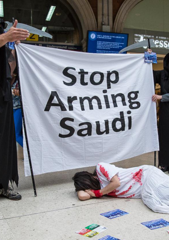 "Activists stand with a banner reading ""Stop Arming Saudi"""