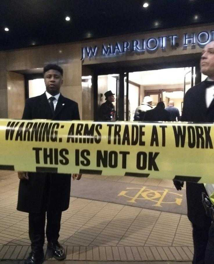"Security guards stand in front of a sign saying ""arms trade at work this is not ok"""