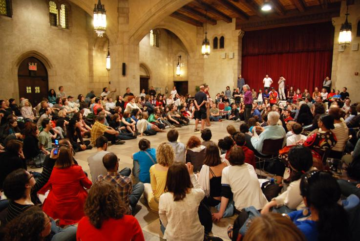 A large group of people take part in a forum theatre exercise