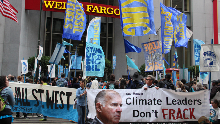 A group of climate activists take action outside a bank
