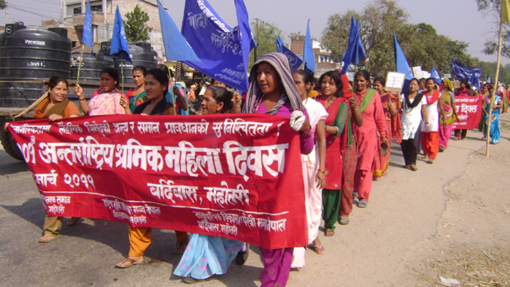 Activists in Nepal marching behind a red banner