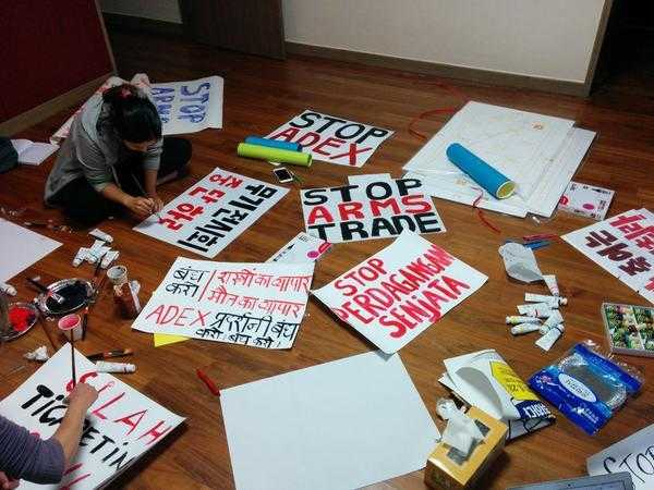 Two activists paint banners and placards in preparation for a protest