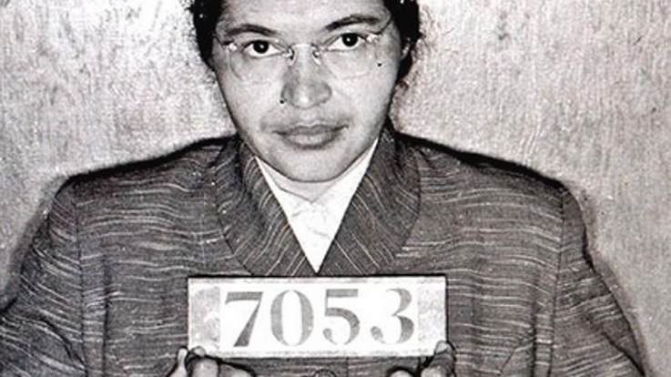 A photo of Rosa Parks holding her arrest number
