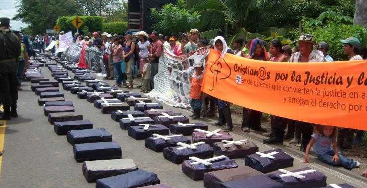Members of the community San José de Apartadó gather behind model coffins, in a protest against violence they face.