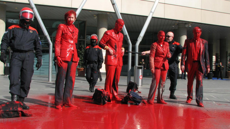 Activists stand in front of a bank, covered in red paint, in a protest against funding of the arms trade.