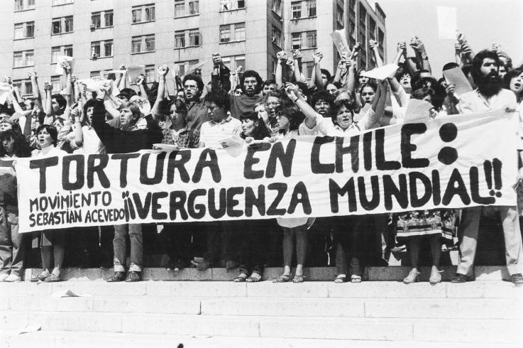 Activists hold a banner condemning torture in Chile