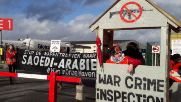 In the foreground an activist stands in a DIY checkpoint barrier. Others hold banners in Belgian, protesting arms sales to Saudi Arabia