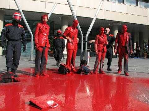 A group of protesters stood in a line, covered in red paint, outside a banks AGM