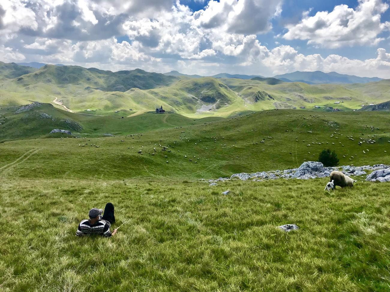The Sinjajevina highlands - rolling green hills. In the background is a small church. In the foreground a man relaxes on the grass. To the right of the photo there is a sheep and lamb.
