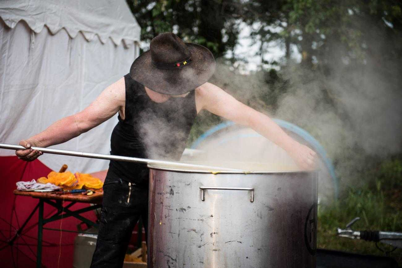 Someone cooks over a large pot. Their face is obscured with a large hat