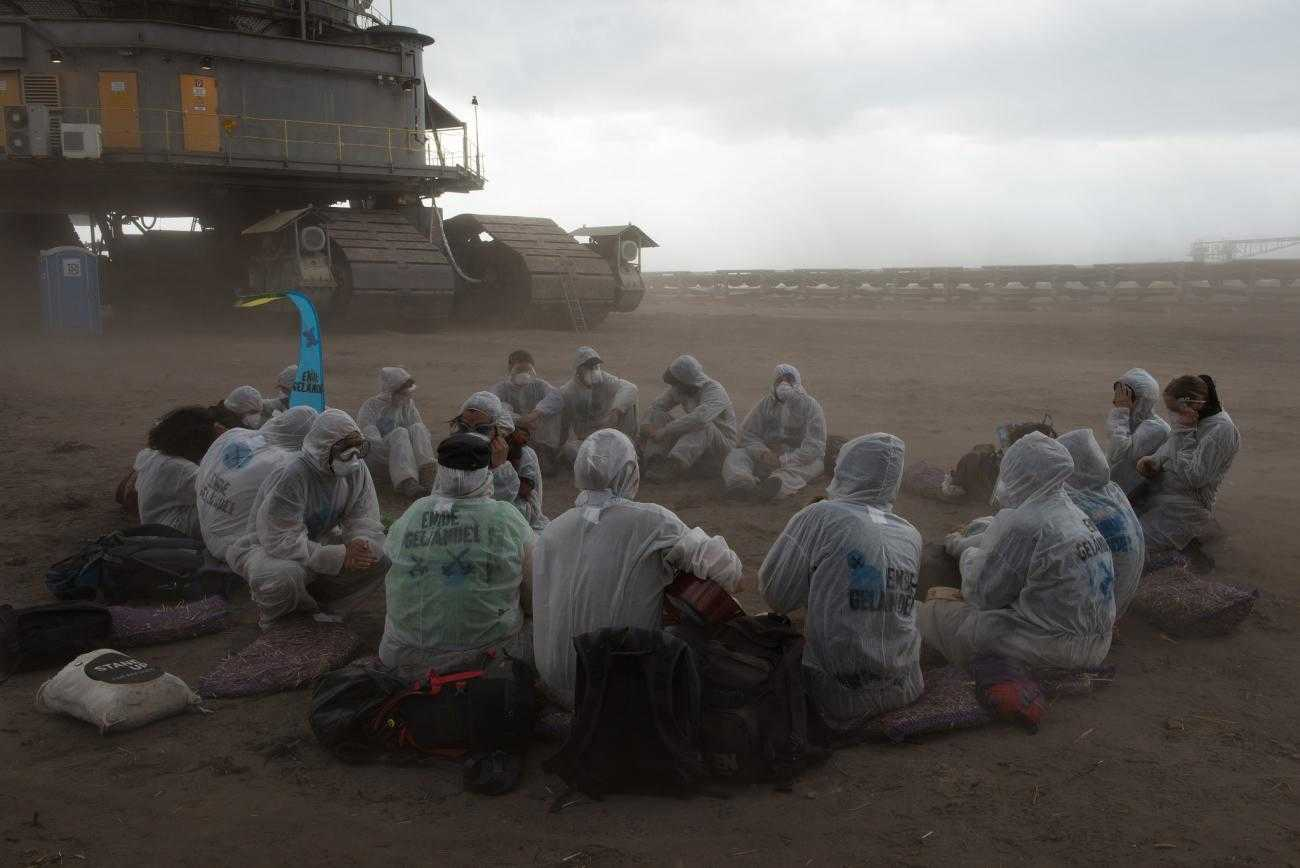 A dozen activists sit on the ground in a dusty coal mine. In the background is a huge piece of mining machinery