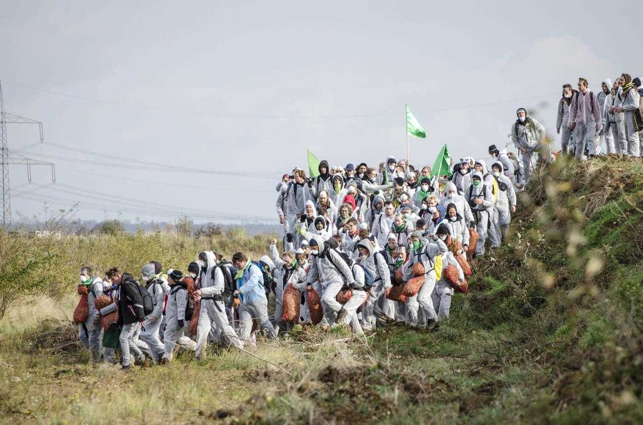 Hundreds of activists dressed in white descend from a hill.