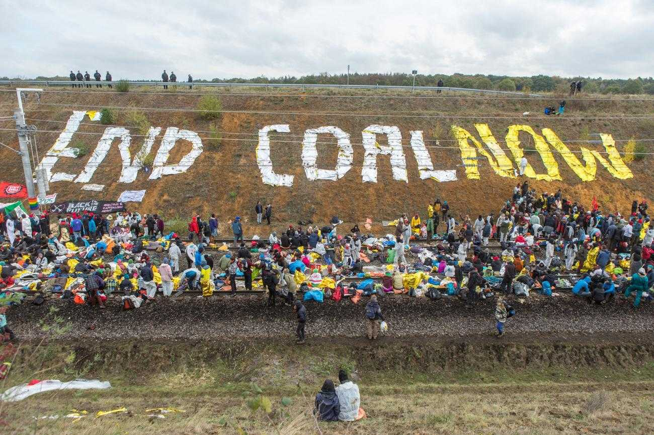 "A large crowd sits on a railway track. On the bank the words ""End Coal Now"" have been spelt out"
