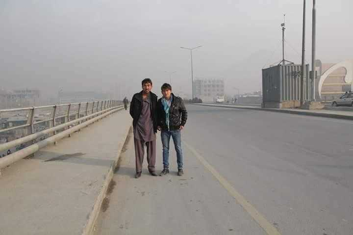 Two men stand in the middle of the photo, in the middle distance. They are on a grey dusty road
