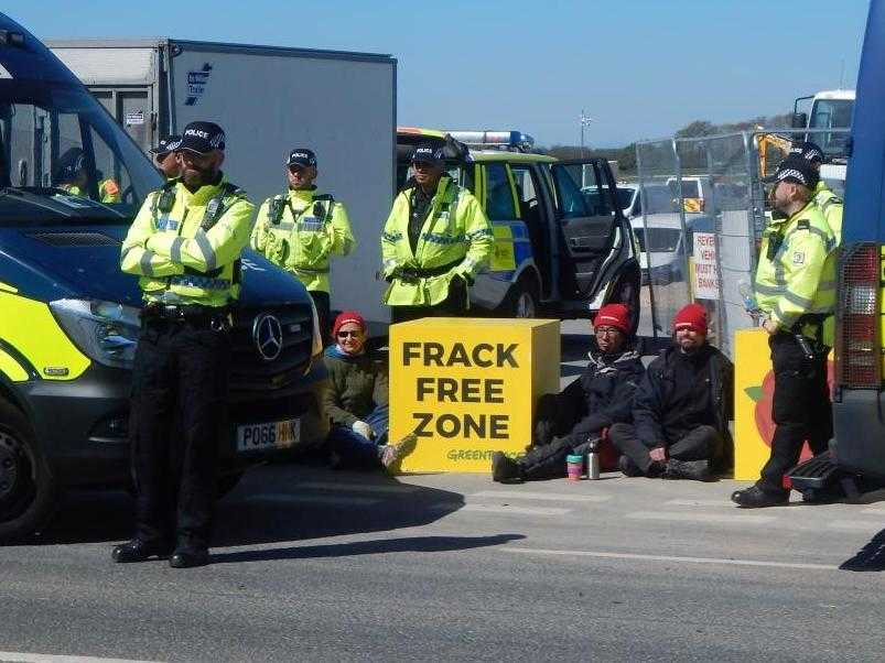 "Greenpeace activists locked on to a large yellow box reading ""Frack Free"""
