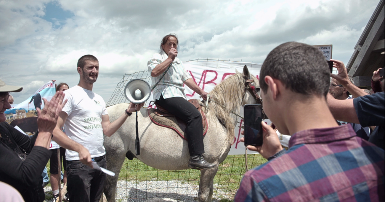 A protester sits on a horse, speaking into a megagphone