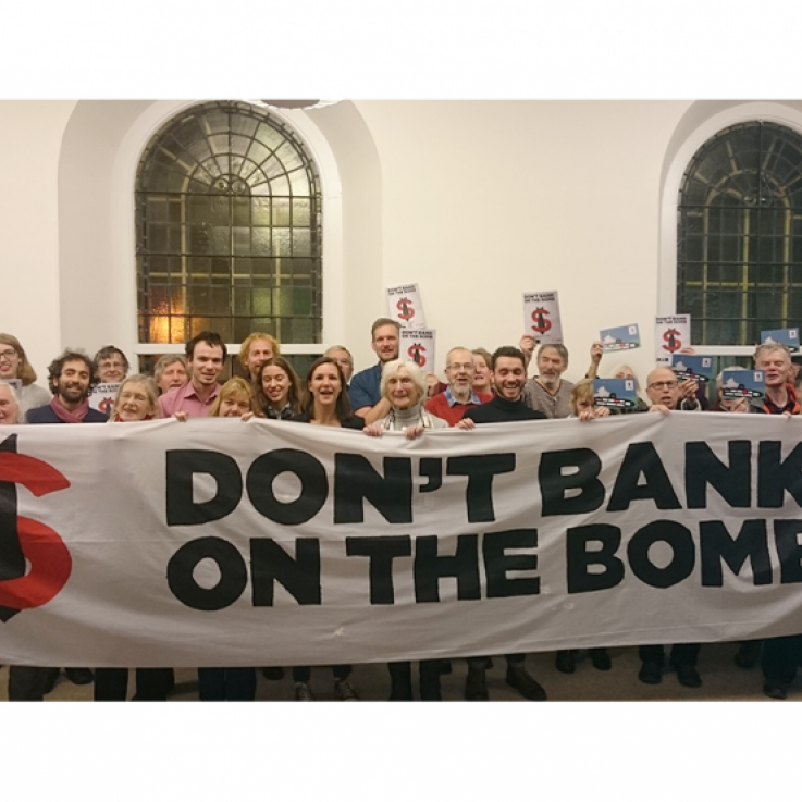 "A large number of people standing behind a banner reading ""Don't Bank on the Bomb"""