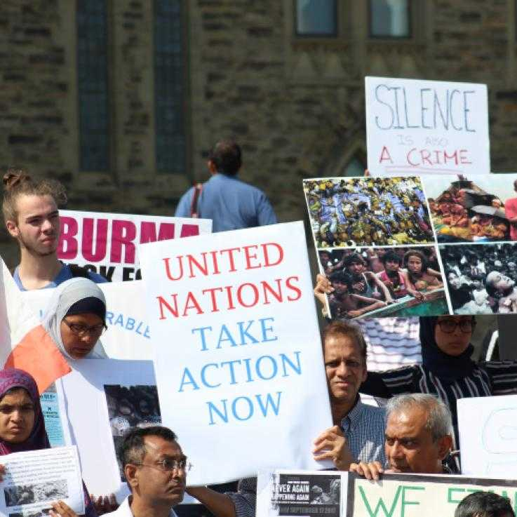 "A protest in solidarity with the Rohingya community in 2018. In the middle of a crowd someone is holding a sign saying ""United Nations Act Now"""