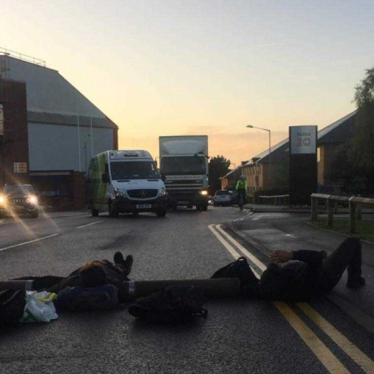 A photo taken at dawn. In the foreground a number of people are lying on the road attached together with metal tubes. In the distance are a number of vehicles on the road.